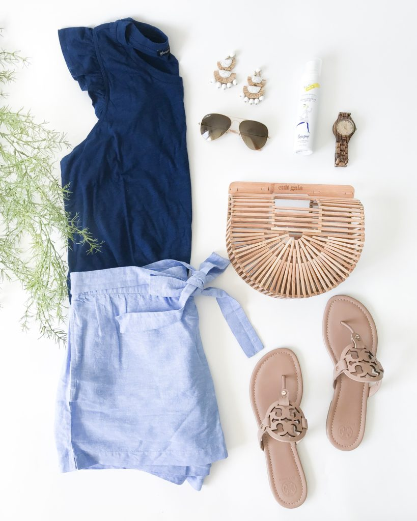 Cute summer outfit! Navy blue ruffle racerback tank, tie-front linen shorts, Tory Burch Miller sandals in Makeup, Cult Gaia Ark Bag and tassel earrings!