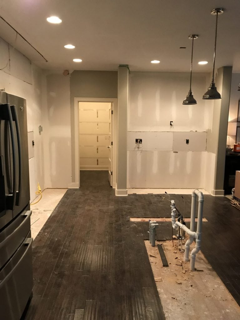 A bare room with pipes and lights and a fridge still there.