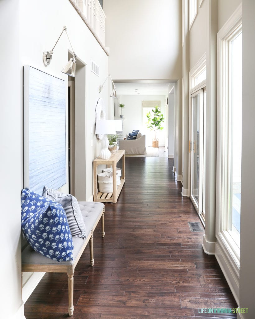 Summer entryway hallway with linen and wood bench, navy blue block print pillow, reclaimed wood console table and swing arm sconces.