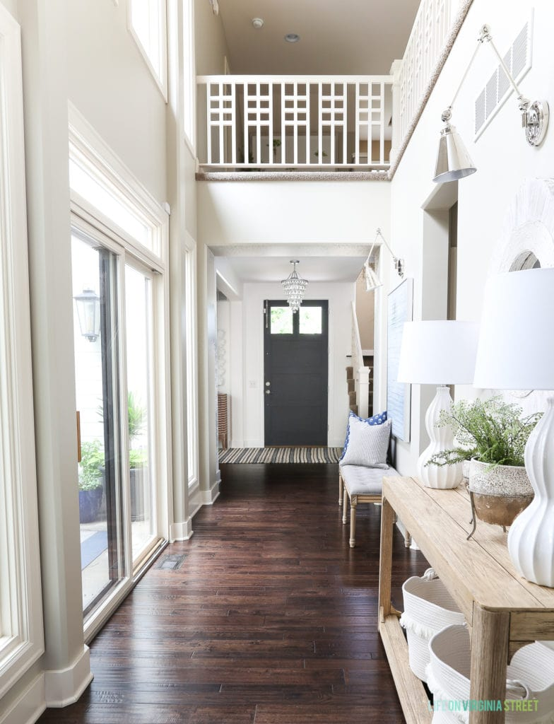 Light and bright entryway with natural wood console table, chrome swing arm sconces, navy blue interior front door, and unique staircase railing.