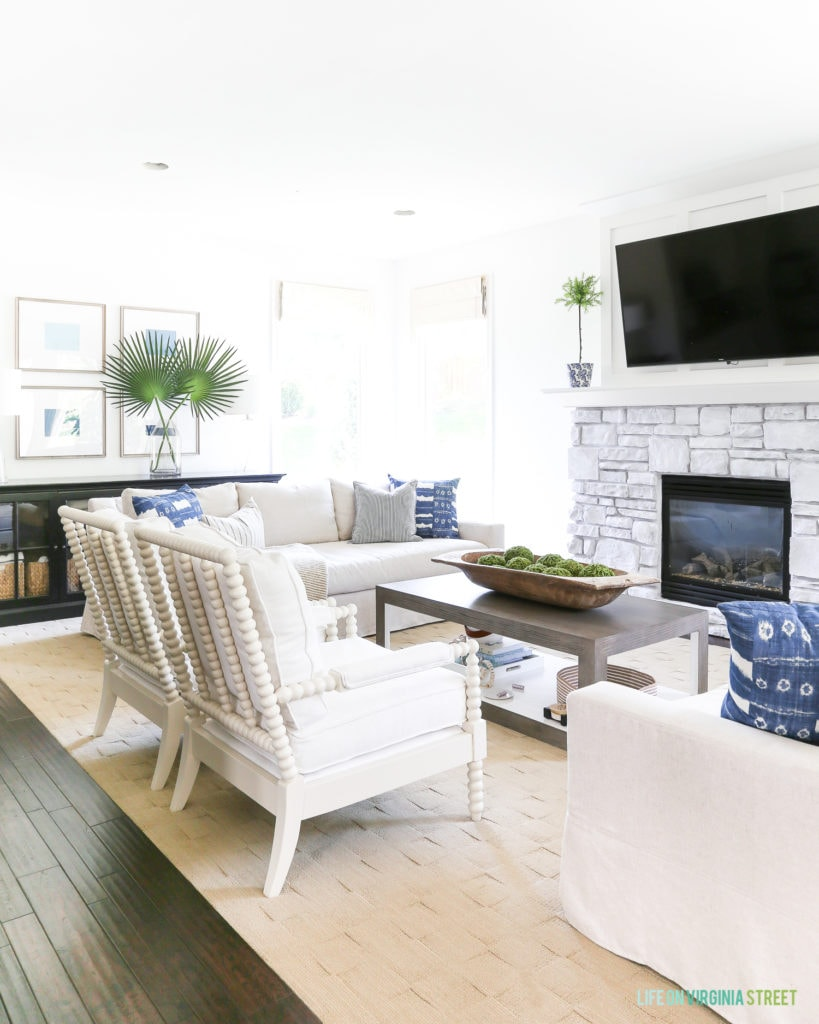 Coastal style living room with white, blue, green, and neutral accents. The space includes spindle chairs and linen slip-cover sofas. Blue and white shibori pillows are accented by striped pillows and ombre blue art. Wall color is Benjamin Moore Simply White.