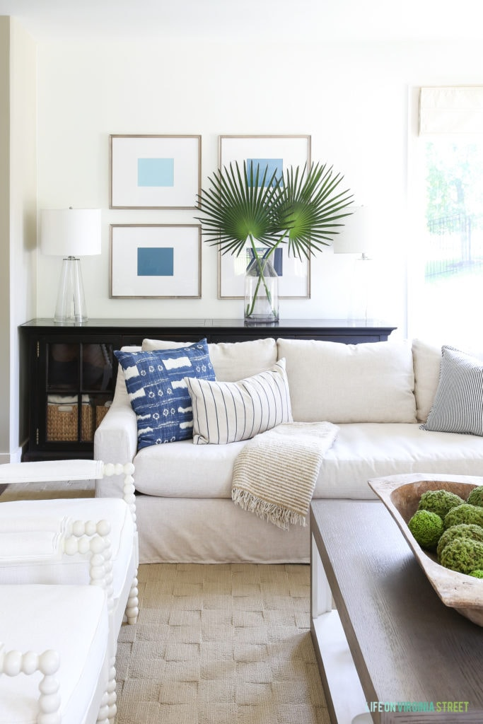 Ombre blue art in driftwood toned frames hang over a linen sofa with blue and white pillows. Accented by palmetto palm leaves.