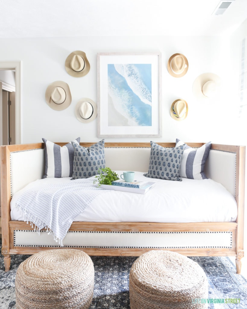 Beach artwork hanging over a wood and linen daybed. This white room is decorated with straw hats on the wall, round jute poufs and a dark blue patterned rug.