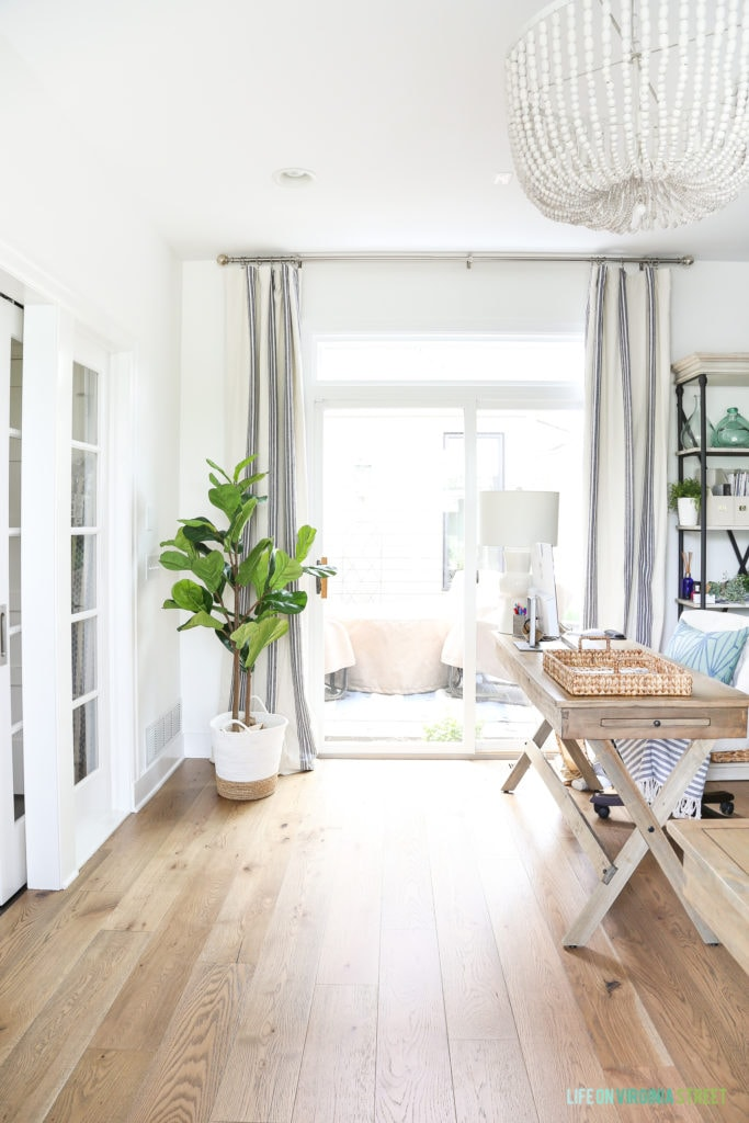 A home office space with white walls and trim, white oak hardwood floors, and white wood bead chandelier and a faux fiddle leaf fig tree. So many great tips for styling faux fiddle leaf fig trees and stems!