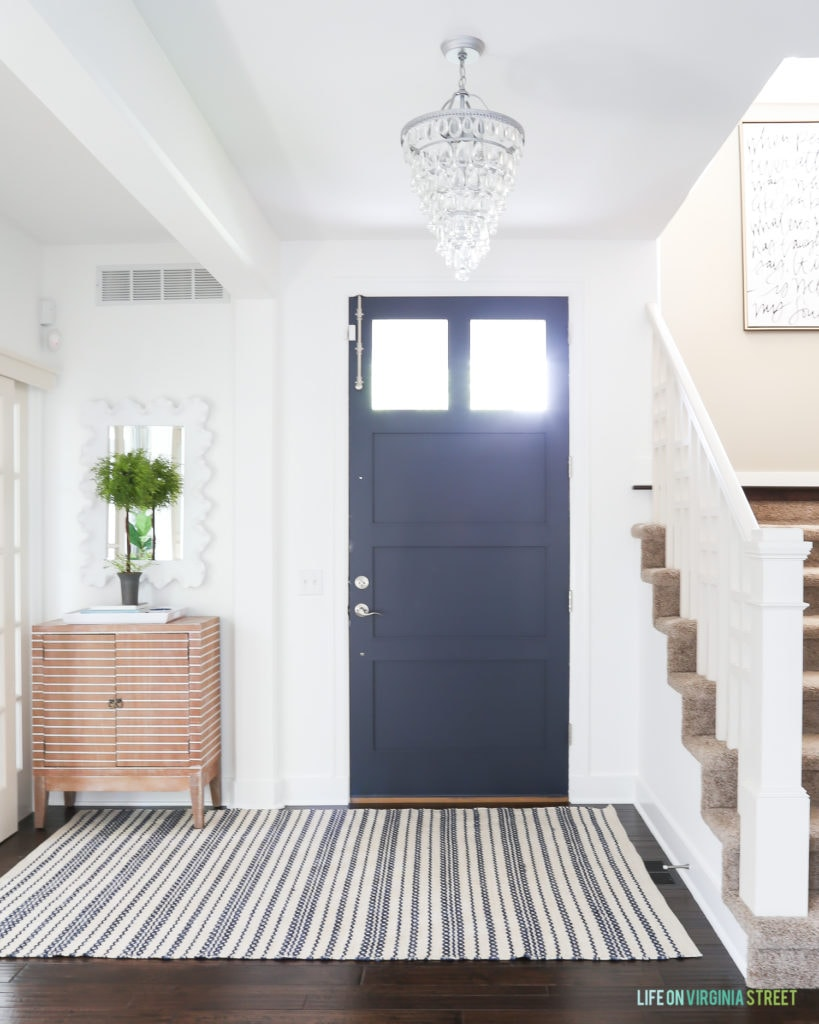 Summer entry with Benjamin Moore Simply White walls and Haley Navy door. The space includes a crystal chandelier, striped wood cabinet, green topiary, and striped rug.