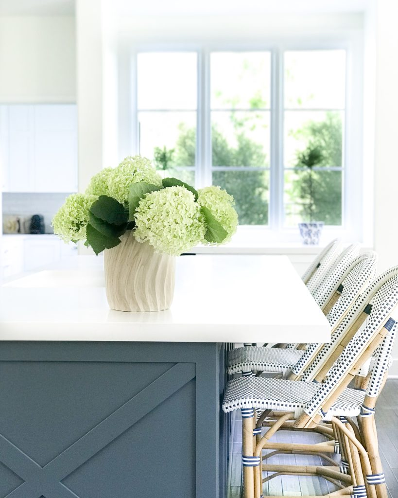 White kitchen with Benjamin Moore Providence Blue island and Serena & Lily bistro counter stools.