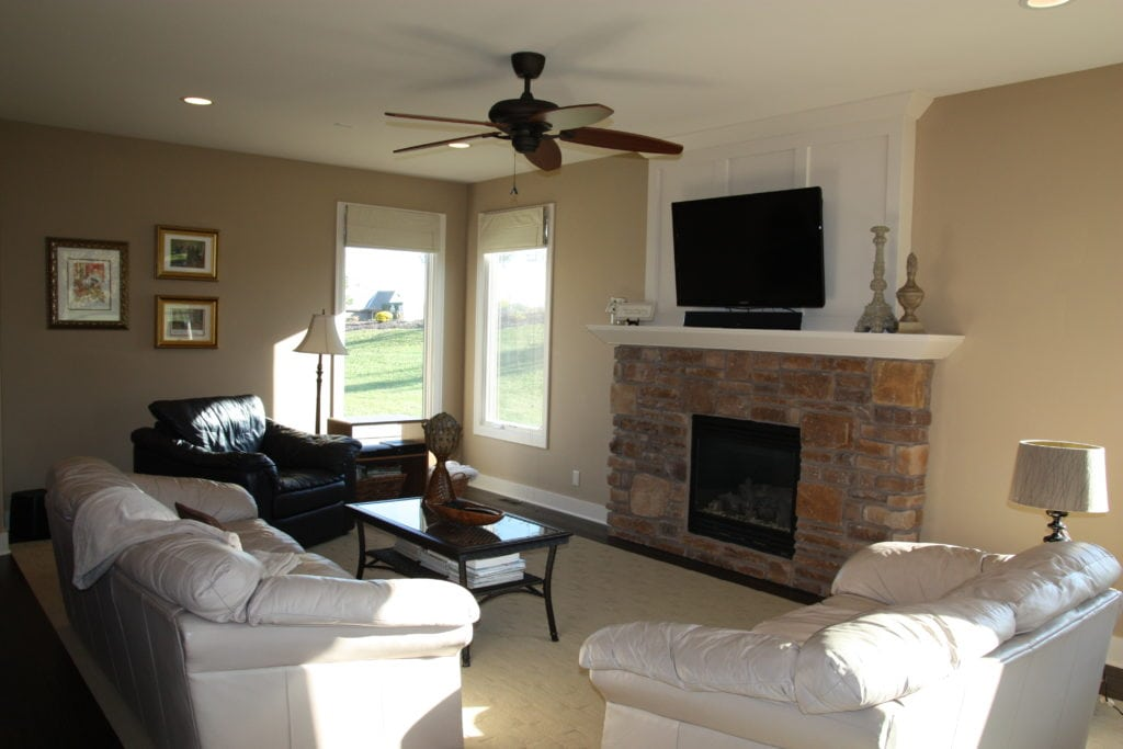 Dark stone fireplace in living room with beige walls and ceiling fan.