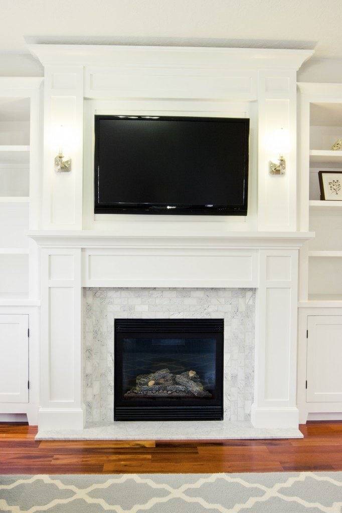 Wooden floor with grey rug and white fireplace with black TV on top of it.