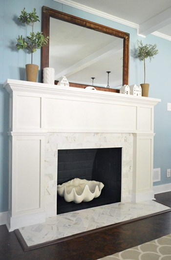 White fireplace with large mirror above the mantel and topiaries on top.