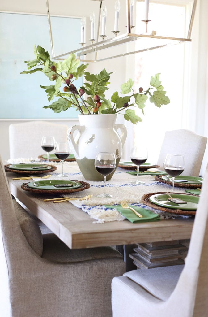 The dining room table with a faux olive branch inside a white and green vase with red wine on the table in glasses.