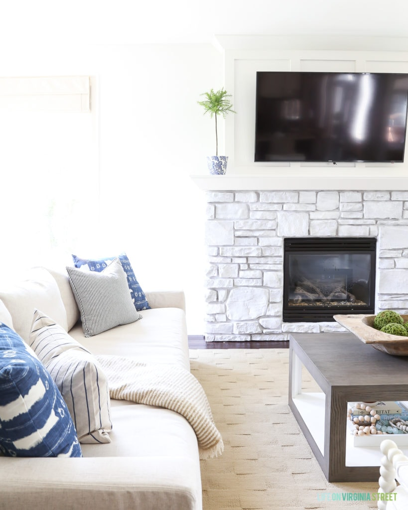White fireplace with TV on mantel and white couches with blue and white pillows.