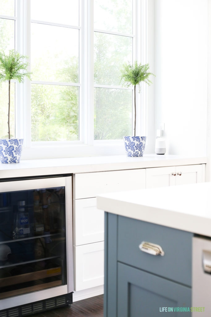 White kitchen with a blue island and topiaries in a blue and white ceramic pot. Google Home blends in perfectly in the space.