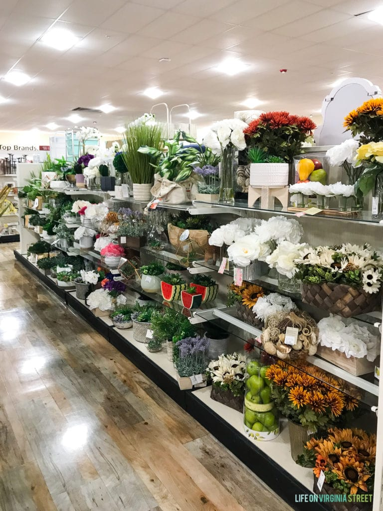Many faux flowers and vases for sale on a store shelf.