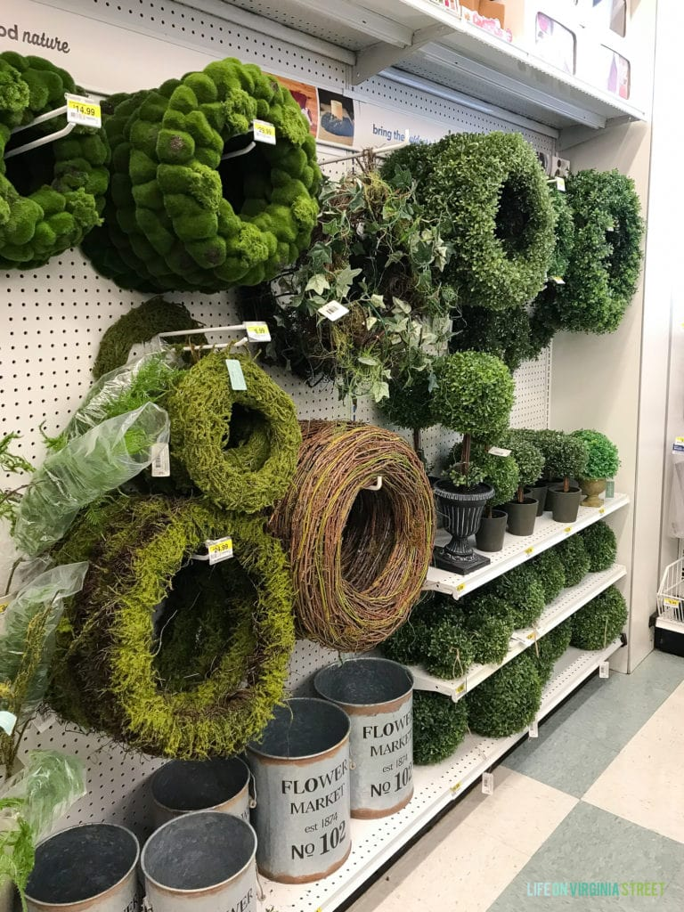 Fake green wreaths on a shelf in the store.