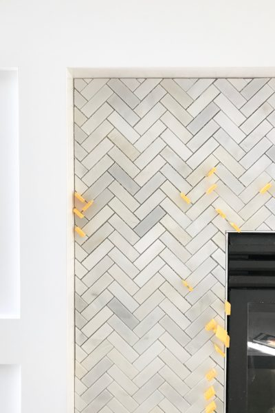 Carrara marble herringbone tile on a fireplace surround.