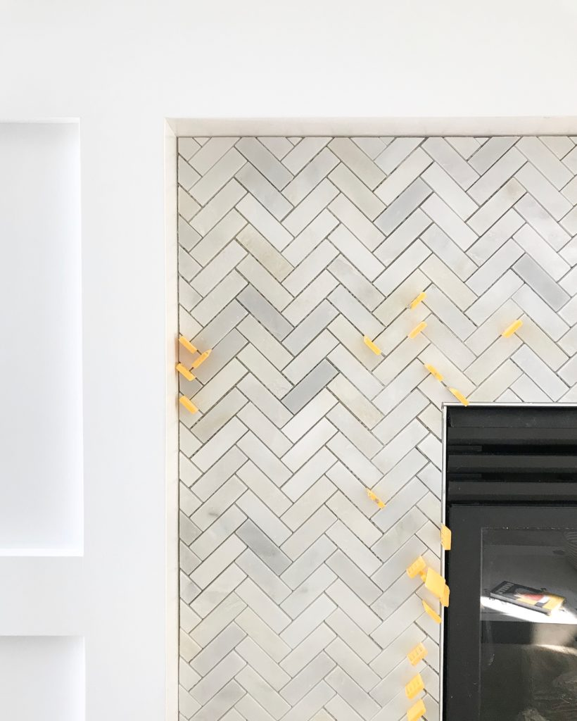 Carrara marble herringbone tile on a fireplace surround.