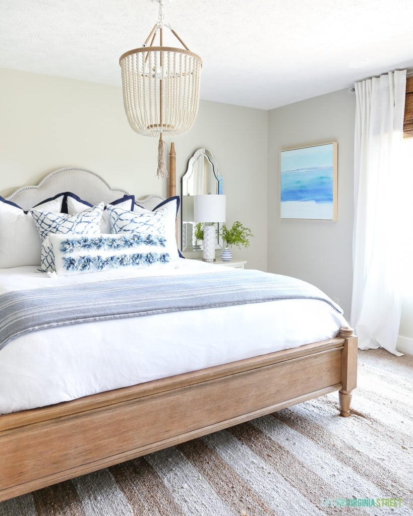 A gorgeous coastal inspired guest bedroom with ocean art, a white bead chandelier, striped rug, and blue and white accents. Such a beautiful and serene bedroom!