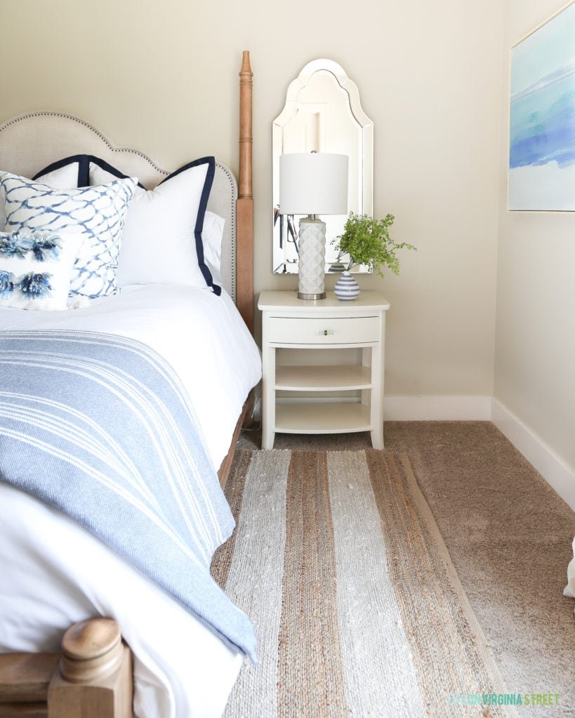 A simple white nightstand updated with new hardware looks perfect in this beachy bedroom.