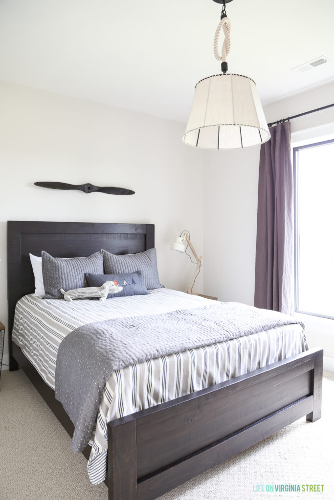 A darker framed bed with headboard, purple curtains and a white light fixture above the bed in the boys room.