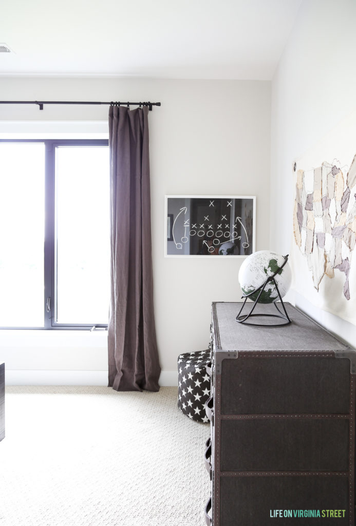 A dark wooden dresser and eggplant purple curtains in the boys room.