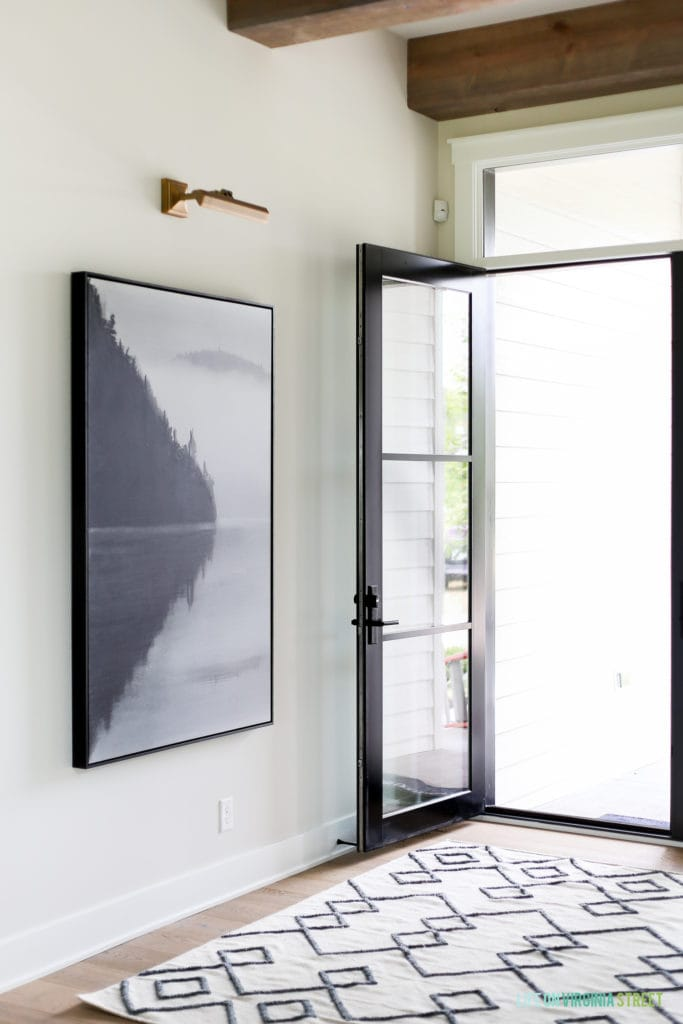 The entryway with a glass door which is open and a small area rug in white and black inside.