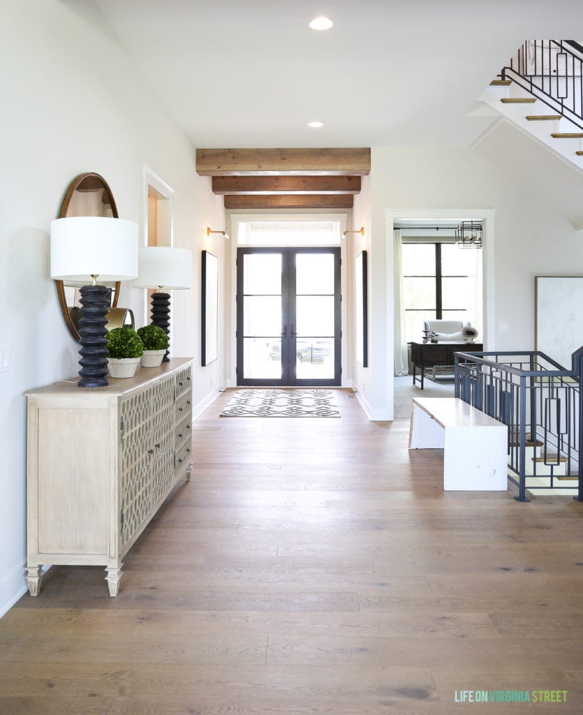 Gorgeous California Modern Farmhouse with white oak harwood floors, reclaimed wood beams, black doors and windows and metal staircase.