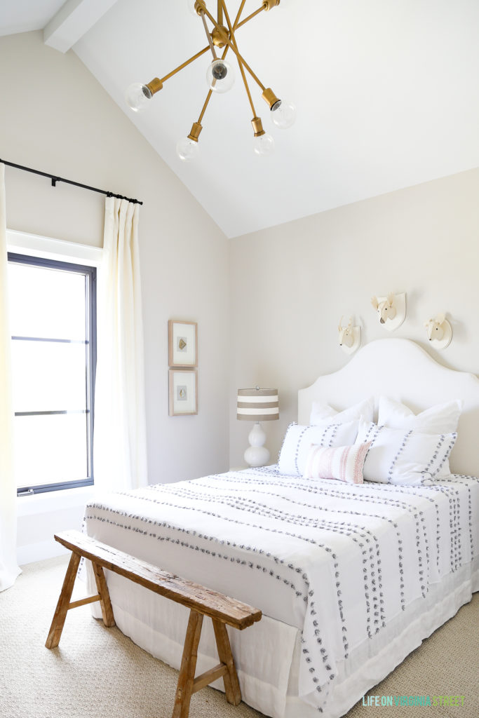 White bedroom with white headboard and white and gray bedding. Gold light fixture and a small wooden bench at the foot of the bed.