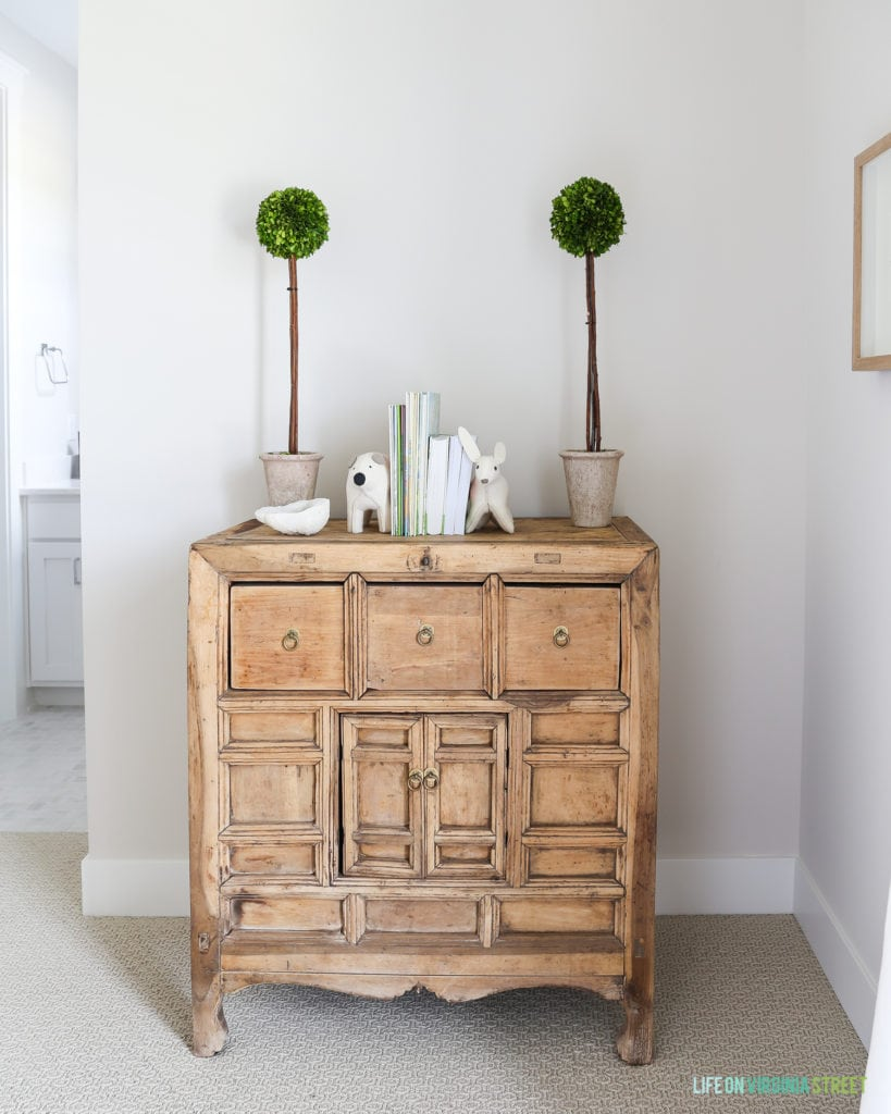 Wooden dresser with green topiary on top.