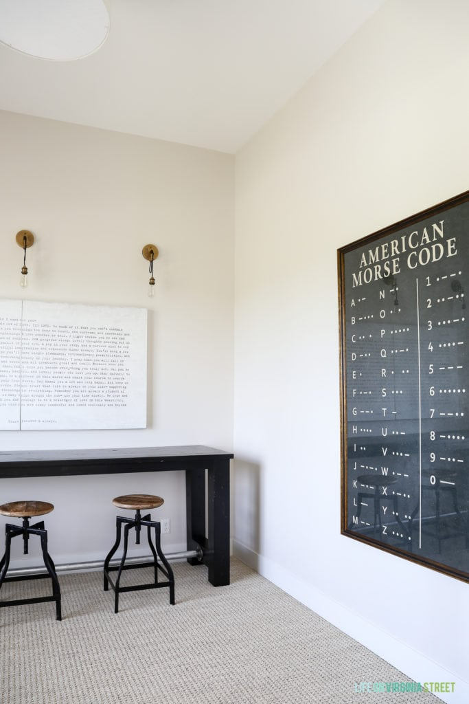 A desk and chairs in the room with a picture of the morse code on the wall.
