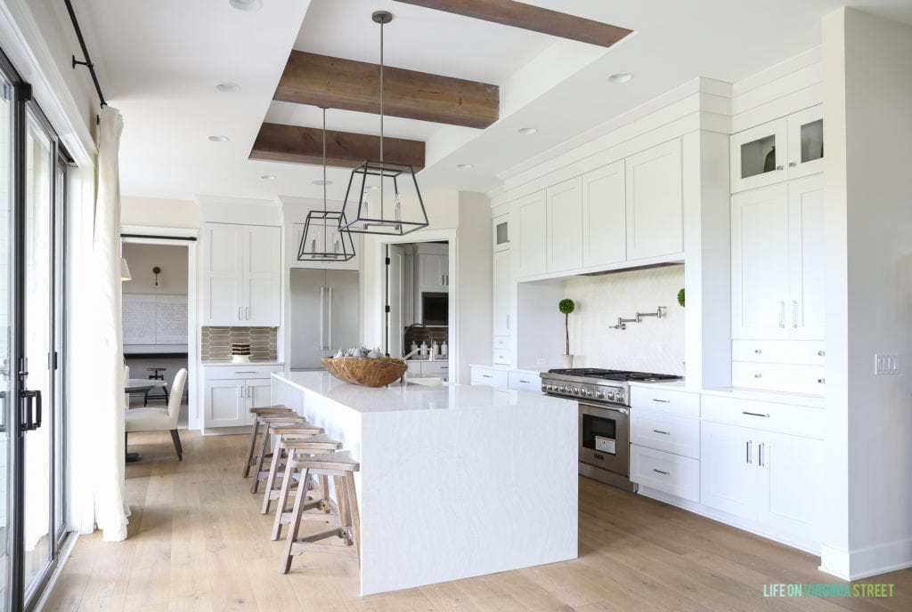 Large white kitchen with wood beams and a white island.