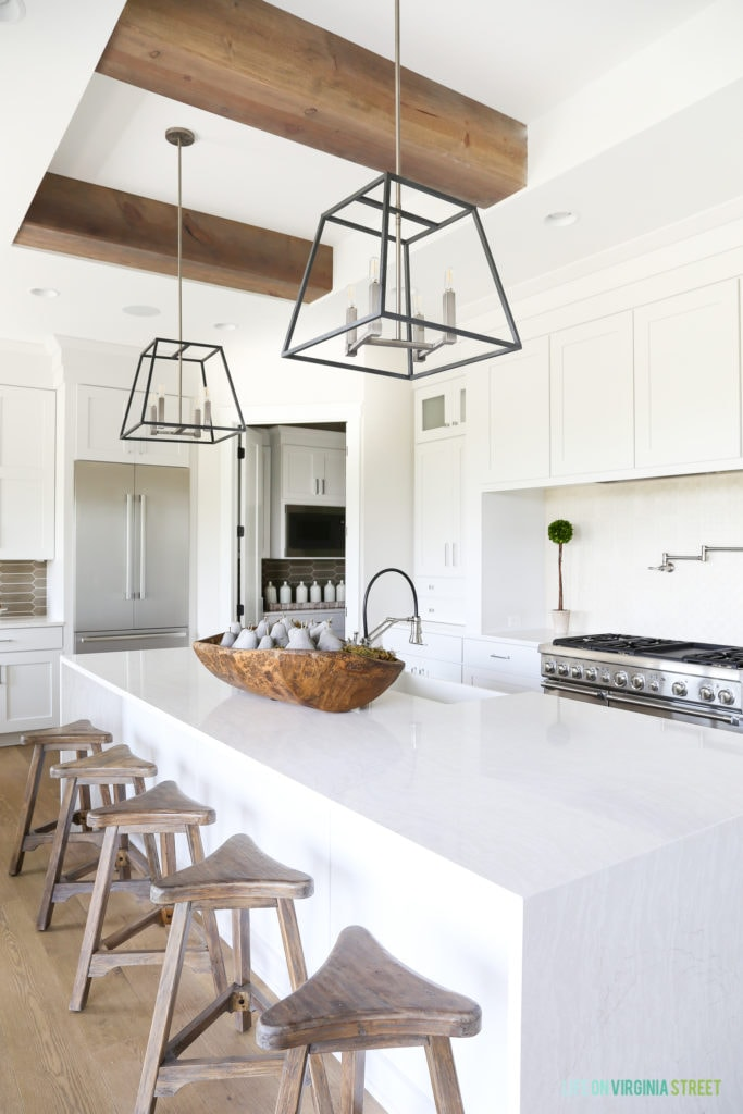A California modern farmhouse kitchen with waterfall island and wood barstools. I love the natural wood beams on the ceiling and the industrial metal light pendants.