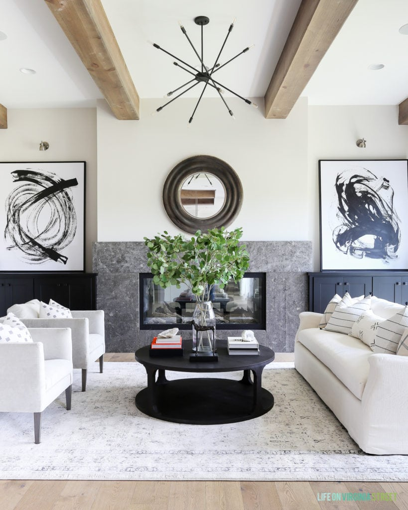 A California Modern Farmhouse from the 2018 Omaha Street of Dreams. I love the combination of natural wood beams with modern details like the sputnik chandelier and graphic black and white artwork. The linen sofa is accented with black and white mudcloth pillows.
