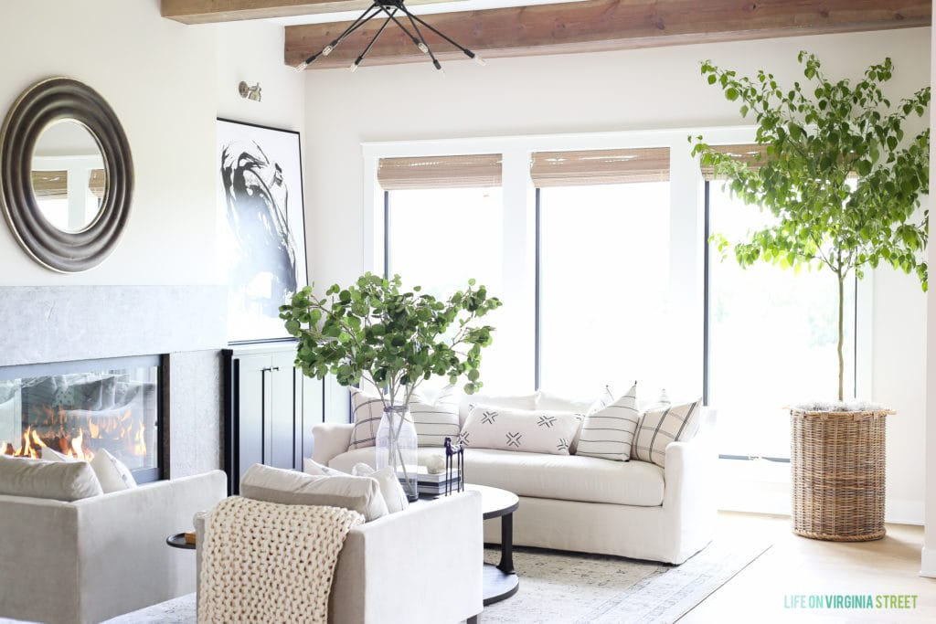 A neutral living room with white couches, a mirror on the wall and large green plants in wicker pots.