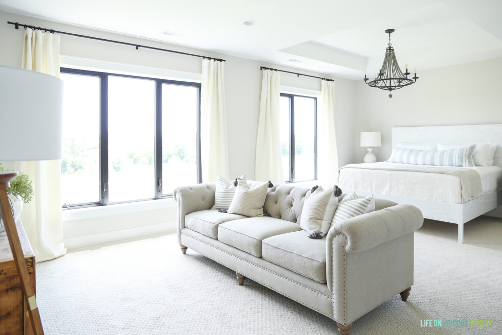 Master bedroom in a white neutral color with a white sofa in the middle of the room.