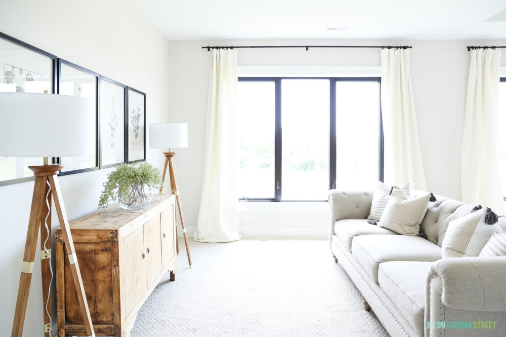 A large window with white curtains in the master bedroom.
