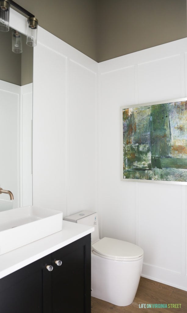 Board and batten carried into the bathroom with artwork on the wall.