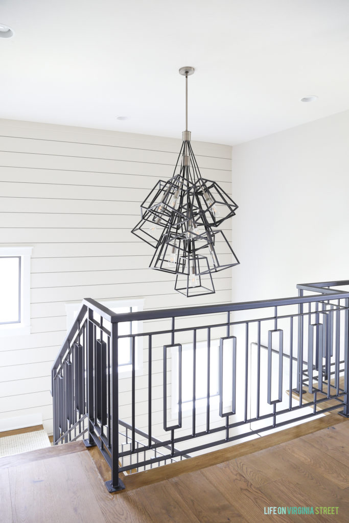 Metal staircase with a metal modern chandelier at the top of the staircase.