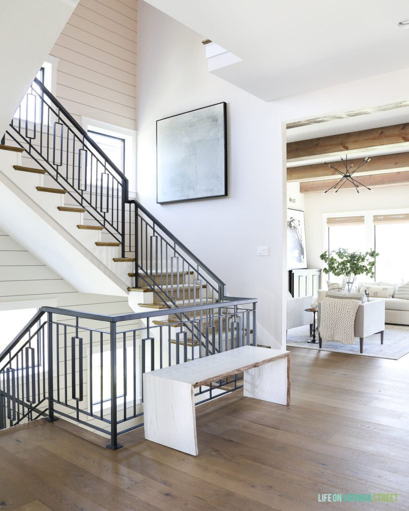 Metal staircase with a shiplap stair well and oversized abstract artwork.
