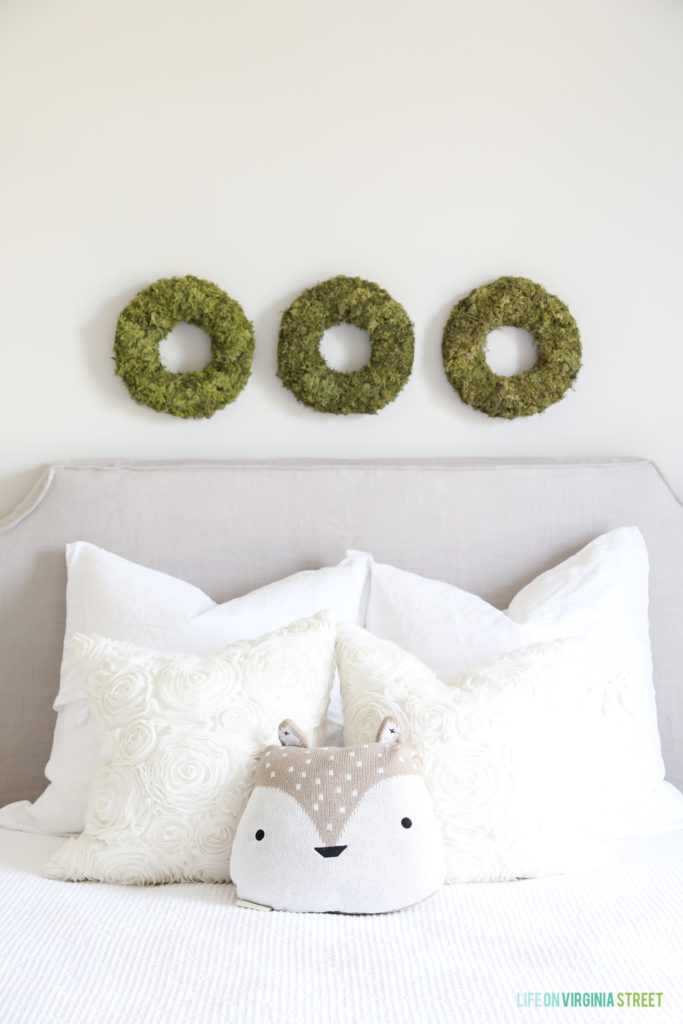 A close up view of the three mossy green wreaths above the bed.