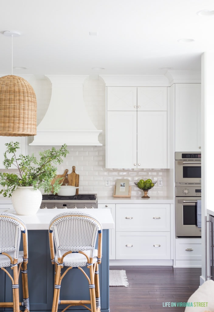 A coastal inspired white kitchen with a blue island. The island has a large white vase with faux greenery underneath a basket pendant light fixture.