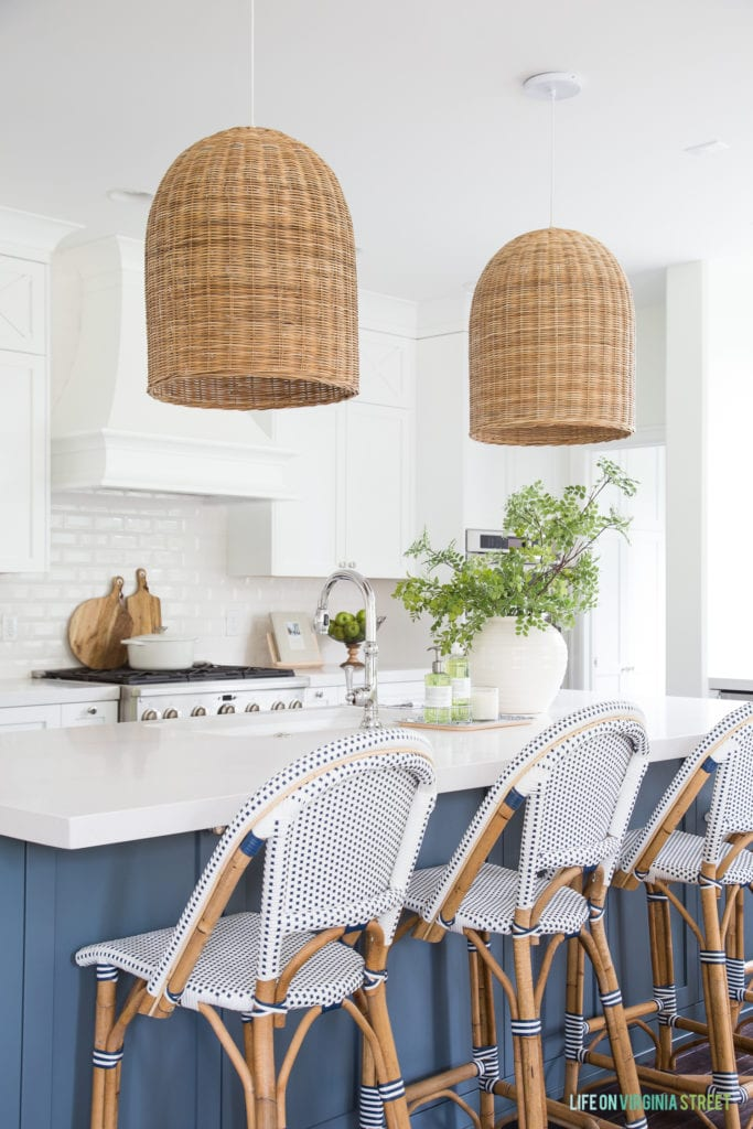 A coastal kitchen with beachy accents including basket pendant lights, a blue island, and woven bistro chairs.