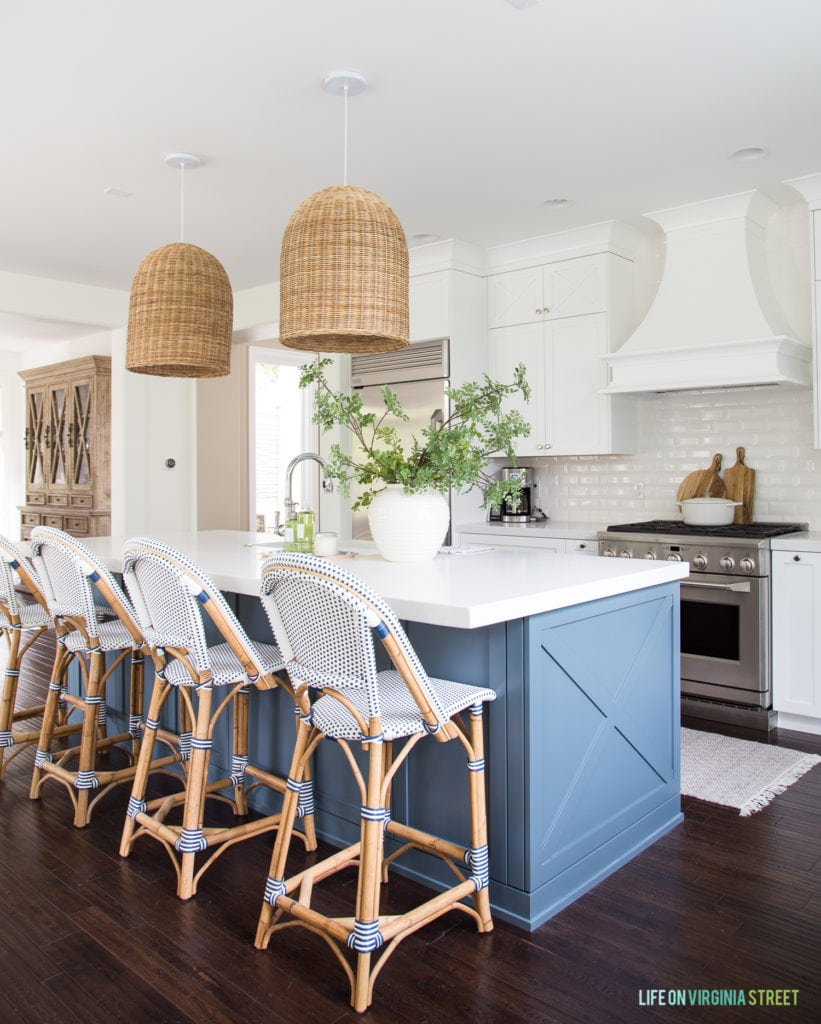 A coastal inspired kitchen with white cabinets, white beveled subway tile, blue island, woven basket pendant lights, blue and white bistro chairs and green and wood toned accents.