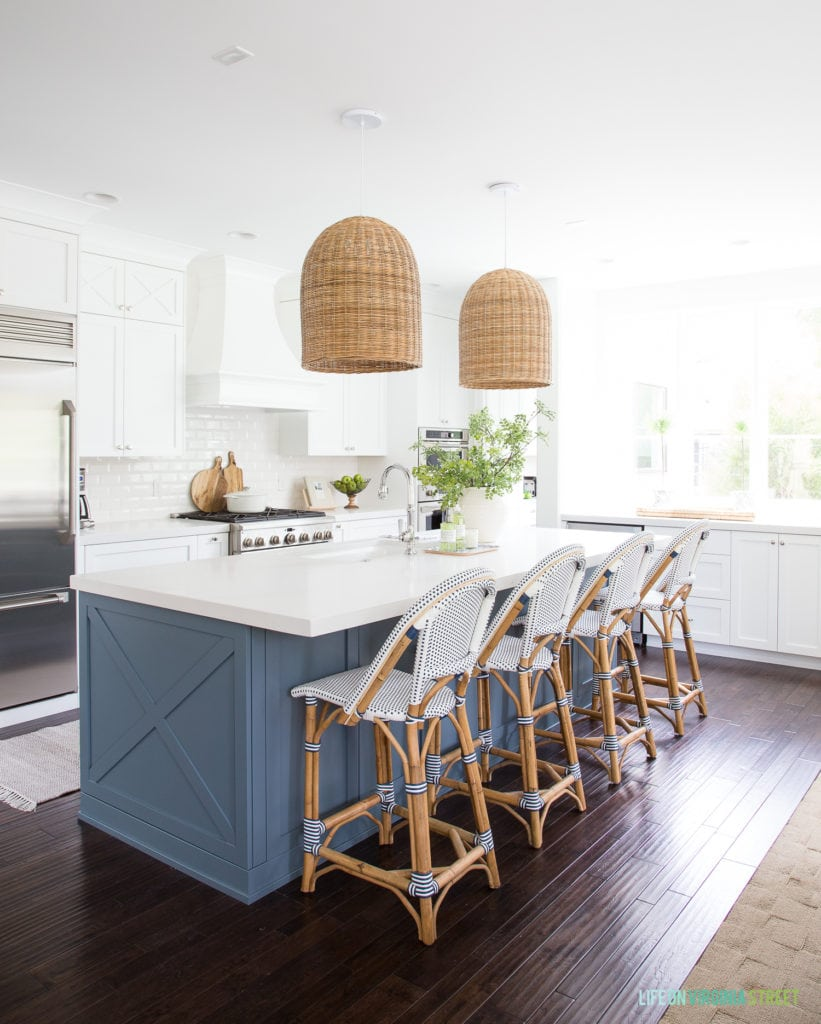 Coastal kitchen with white cabinets, blue island, basket pendant lights, bistro counter stools and a large window. Wall and cabinet colors are Benjamin Moore Simply White, island is Benjamin Moore Providence Blue and countertops are Caesarstone Calacatta Nuvo.