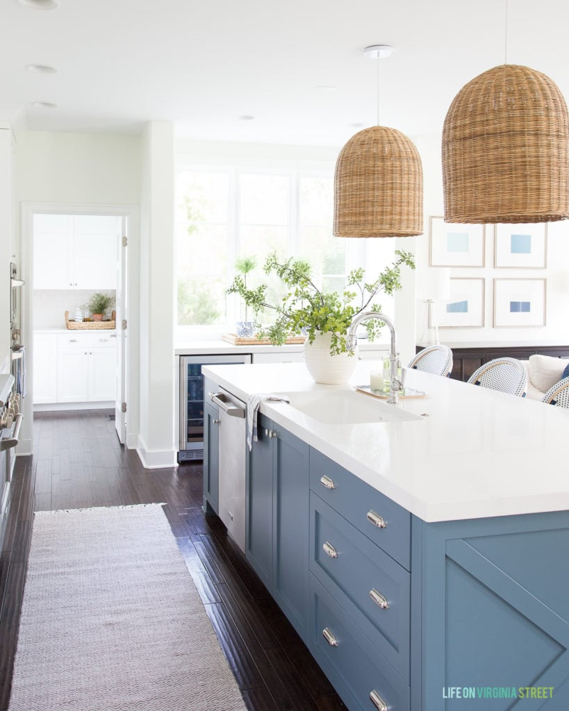 A blue kitchen island with chrome hardware, Caesarstone Calacatta Nuvo countertops, basket pendant lights and green and blue accents.