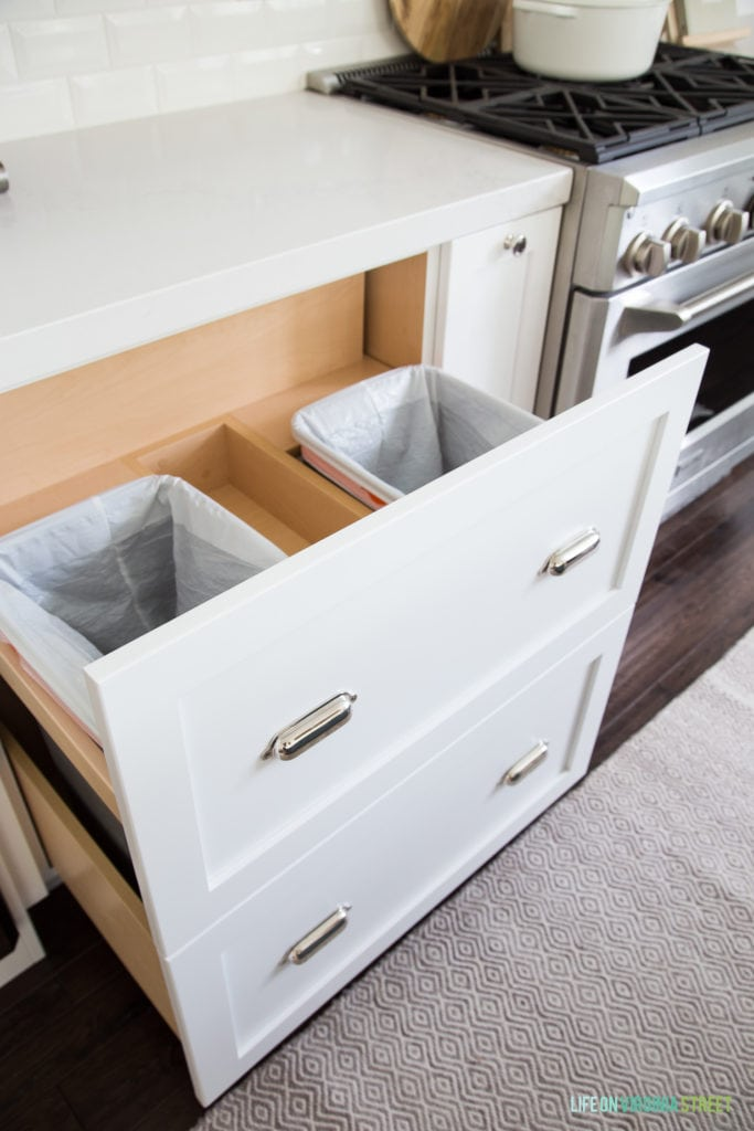Custom pull-out garbage can drawer in a white coastal kitchen. Built by McClain's Custom Cabinets.