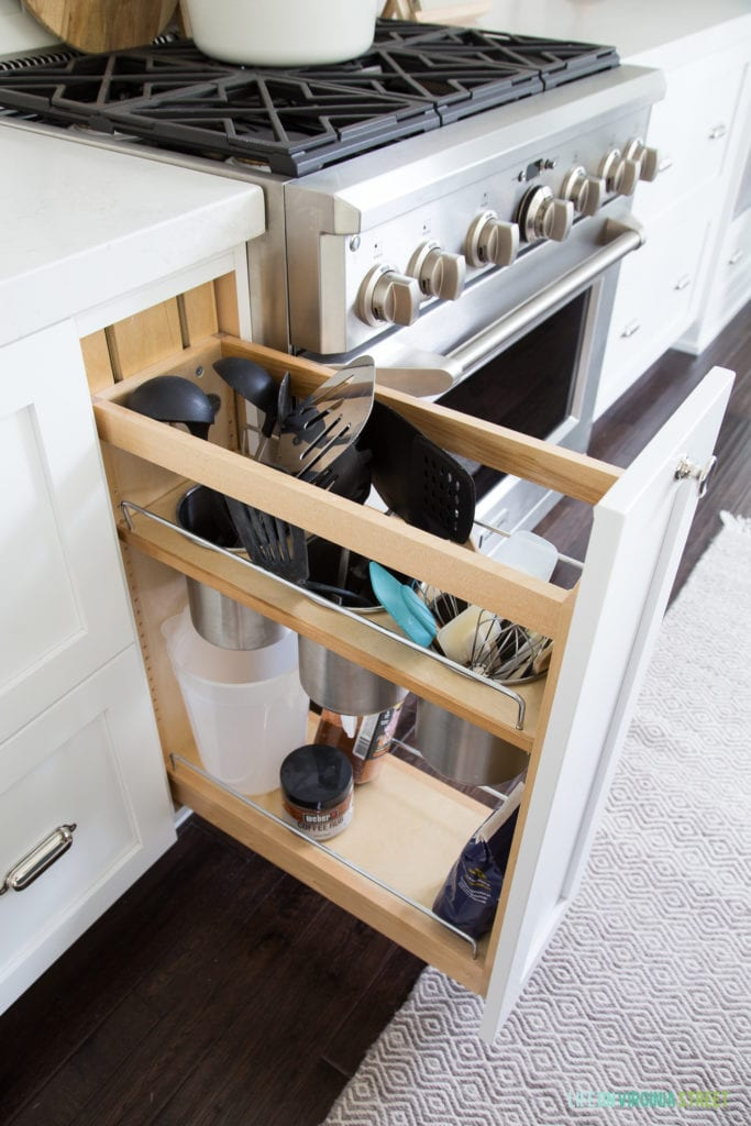 White kitchen cabinets with a pull-out rack for utensils.