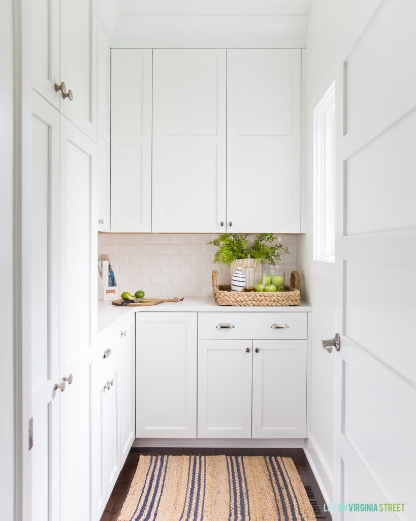 A gorgeous pantry with white cabinets, jute and sisal accents, and a natural and blue striped rug.