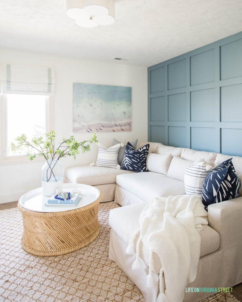 A cozy living room den space with a linen sectional, jute rug, round coffee table, beach art, and blue and white pillows, all in front of a blue board and batten wall.