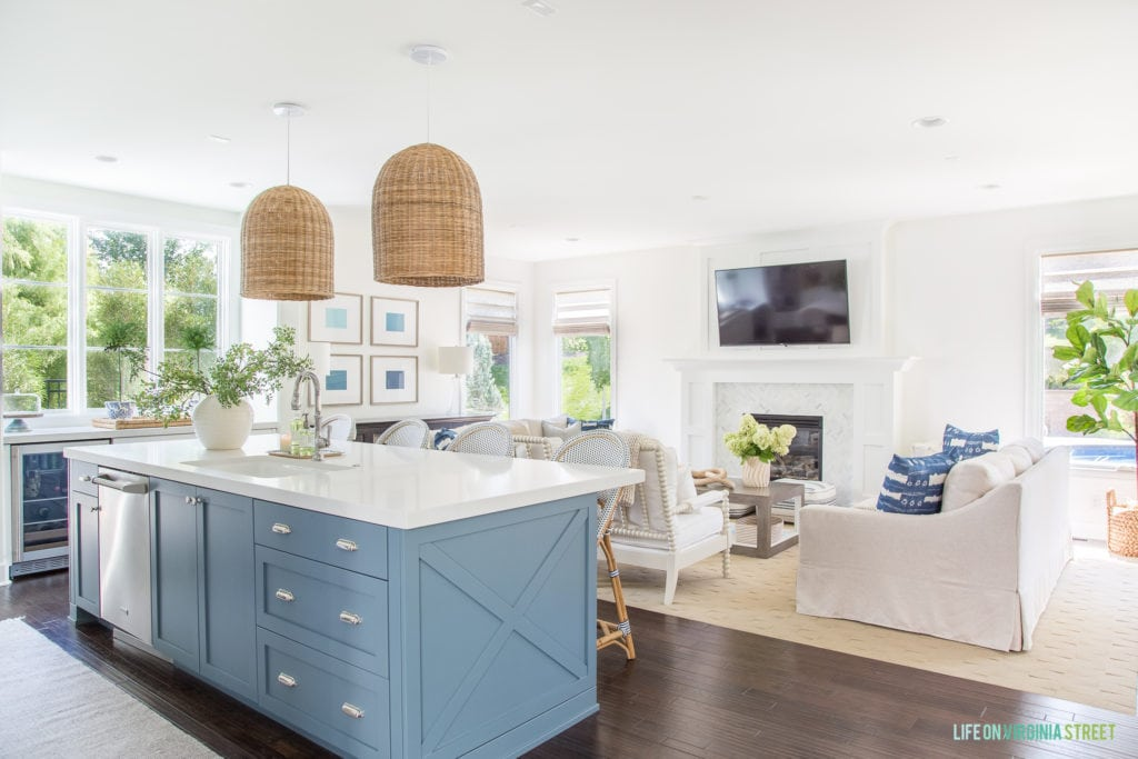 A coastal inspired blue kitchen island and white living room. I love the blue shibori pillows, white spindle chairs, natural woven pendant lights and touches of green.