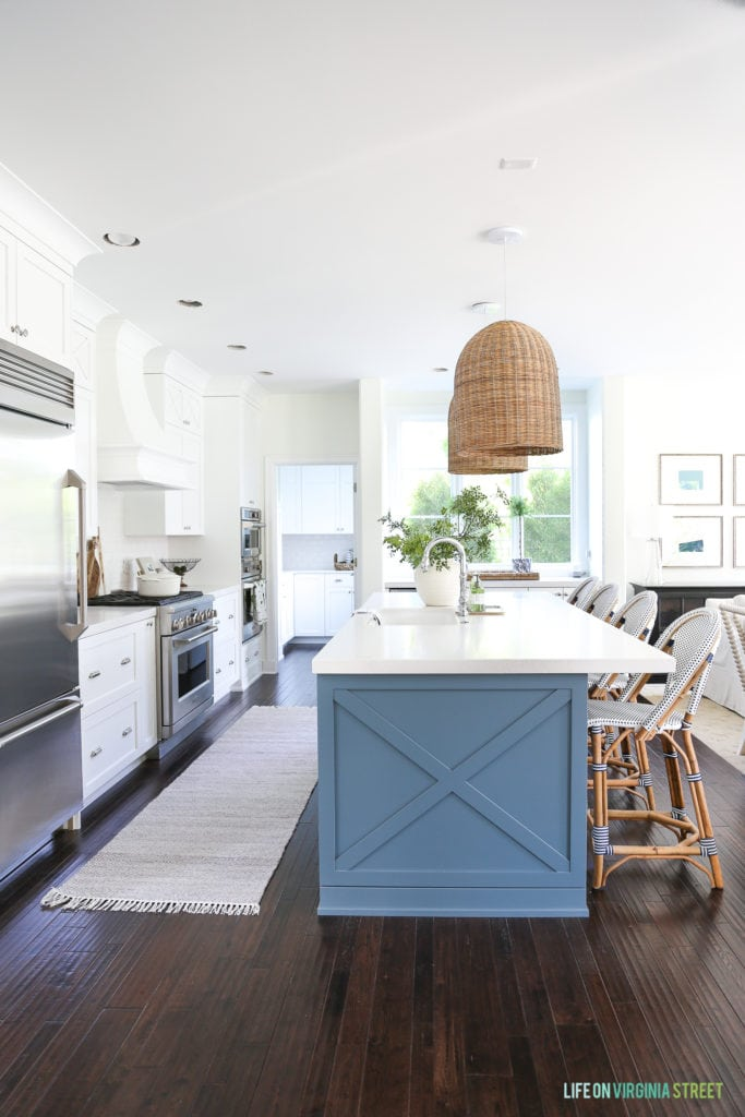Beautiful coastal inspired kitchen with Benjamin Moore Simply White walls and cabinets. The island is Benjamin Moore Providence Blue.